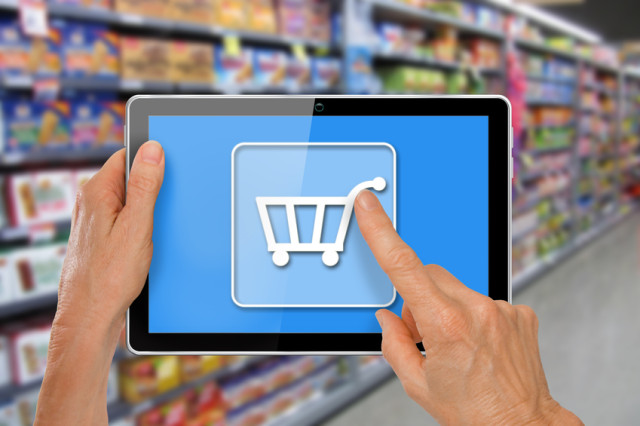 Online Supermarket Shopping Hands with computer tablet touching shopping cart icon in front of supermarket groceries