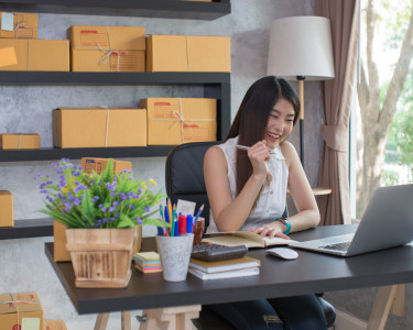 young woman business owner smiling and looking computer in  her homes